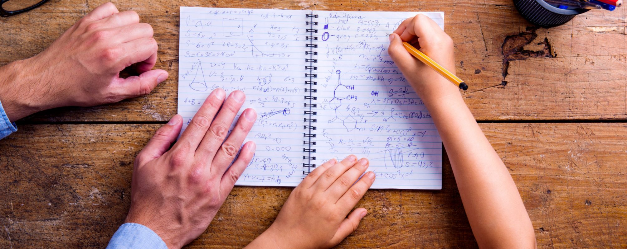 Unrecognizable father and son studying together, writing into a notebook. Studio shot on wooden background. Flat lay.
